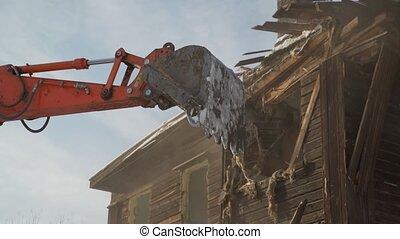Close-up bucket destroys the old wooden building. Car Demolition