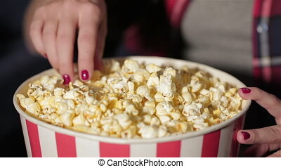 Close up bucket of popcorn and a hand of the girl