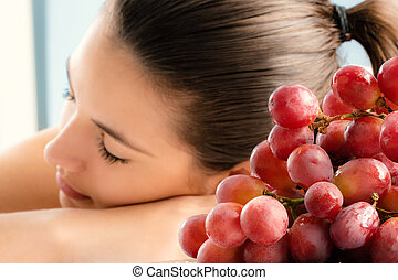 Close up bunch of red grapes with girl in background.