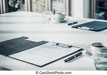 Close up business contract paper on meeting room table with pen and coffee cup in sun light shadow with green plant at office,business agreement concept.