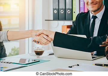 Close up Business women shaking hands during a meeting in the office with blurred business happiness people :business team partnership concept