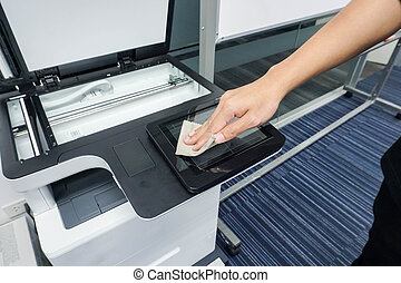close up businessman hand clean printer touch screen for maintenance
