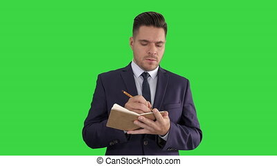 Businessman putting down ideas and filling in checklist on a Green Screen, Chroma Key.