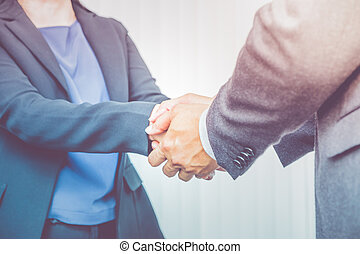 Close up businesswoman and businessman shaking hand for congratulation for success of business concept,Filter color effect.