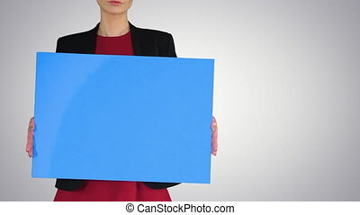 Businesswoman holding blank whiteboard sign on gradient ...