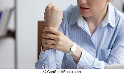 Close up businesswoman holding writs, suffering from carpal tunnel syndrome