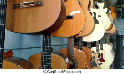 Close-up camera along acoustic and electric guitars in the store of musical equipment