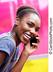 candid portrait of happy young black woman talking on cellphone
