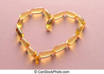 Close up capsules of fish fat oil in the heart shape, omega 3,