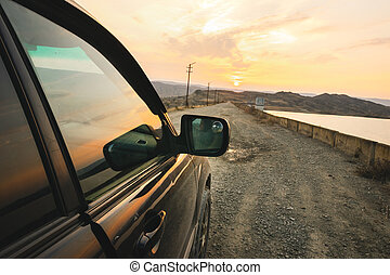 Close up car view on gravel road on the bridge with sunset in the background. Chachuna managed reserve road