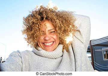 Close up carefree young african american woman smiling outside