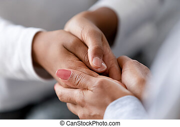 Close up caring African American mother holding child hands