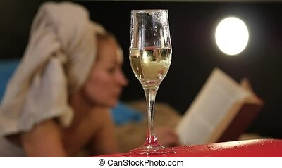 close-up champagne flows into a glass. Beautiful woman lies on a bed and reads a book. slow motion