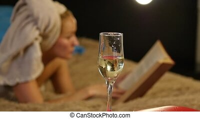 close-up champagne flows into a glass. Beautiful young girl resting comfortably on a bed and reads a book. slow motion