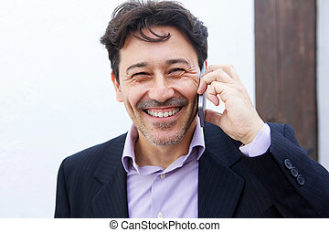 Close up cheerful mid adult businessman talking on mobile phone