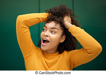 Close up cheerful young african american woman laughing with hand in hair by green background and looking away