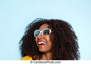 Close up cheerful young african woman in sunglasses looking away and laughing on blue background