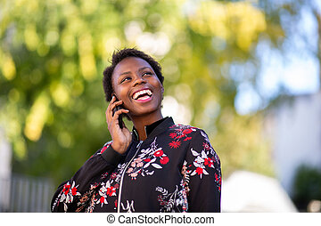 Close up cheerful young african woman talking with mobile phone outdoors