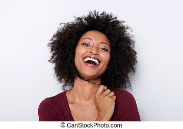 Close up cheerful young african woman with hand in hair and laughing