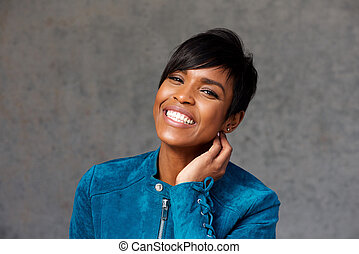 Close up cheerful young black woman against gray background
