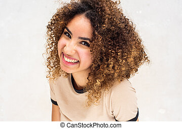 Close up cheerful young woman with curly hair against white background