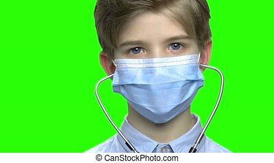 Close up child boy wear medical protective mask and stethoscope.