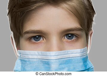 Close up child boy wearing medical mask.