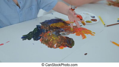 close-up children draw their fingers on paper using paints