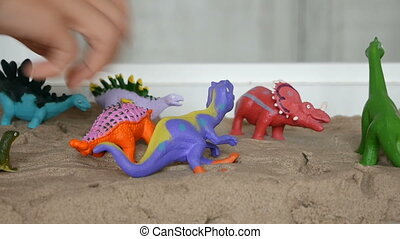 Close-up children plays with sand and dinosaurs on kinetic sand