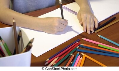Close-up child's hands are drawing with colored pencils. ...