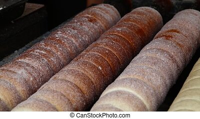 Close up chimney cake baking and rolling - Close up sweet...