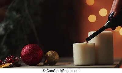 Close-up. Christmas the hand of a young woman lights candles near the Christmas tree on the background of the blurred background