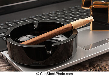 Close-up cigar in the ashtray standing on a laptop.