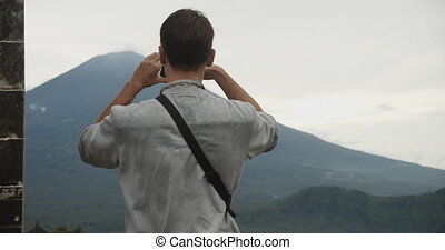 Close up circling view of a man standing between the Gates of Heaven black stone pillars in Pura Penataran Agung Lempuyang temple and taking pictures of Mount Agung volcano on his phone. 4K