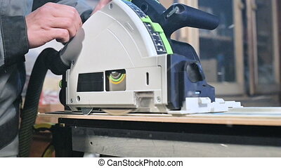 close-up circular saw on the slider cuts off the edge of the chipboard plate in slow motion