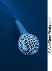 Close up classic microphone with cable over dark blue