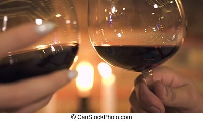 Close up clinking wine glasses on burning candles background. Man and woman clinking wineglasses at romantic dinner for two with candles.