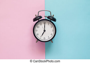 Close up clock on pink and blue background, Pastel colors concept