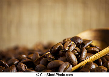 Close up coffee beans on wooden background.