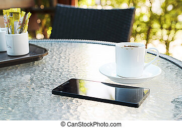 Close up coffee cup with smartphone on coffee table backgrounds