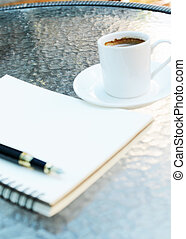 Close up coffee table area with blurry notebook and pen and coffee cup