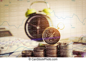 Close up compass on pile of coins with alarm clock and stock market information graph.