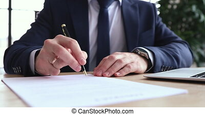 Close up concentrated young businessman in formal wear carefully reading contract terms of conditions, putting signature on paper. Focused executive ceo signing report after checking information.