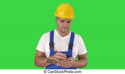 Construction worker writing to do list or checklist on a...
