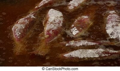 Close up cooking deep fried red mullet fish in oil - Close...