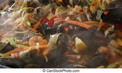 Close up cooking seafood saute stew in frying pan - Close up...