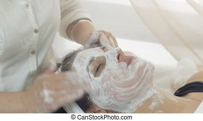 Close up cosmetologist hands, face rub in mask into girl face in beauty saloon