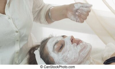 Close up cosmetologist hands rub in white mask into girl face in beauty saloon