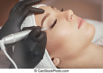 Close up of professional cosmetologist wearing black gloves making permanent eyeliner makeup for young woman. Client lying on couch at beauty salon with closed eyes and enjoying.