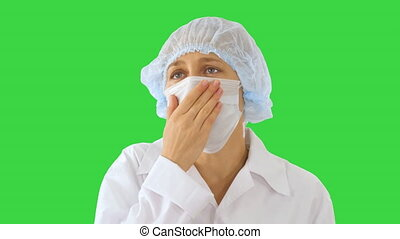 Coughing Female Doctor in a Mask To Prevent Others From Infection on a Green Screen, Chroma Key.
